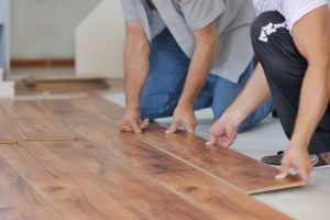 two men laying down laminate flooring