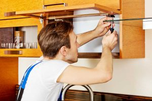 handyman updating old kitchen cabinets